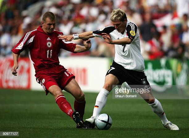 Bastien Schweinsteiger of Germany holds off Andrejs Prohorenkovs of Latvia during the UEFA Euro 2004 Group D match between Latvia and Germany at the...
