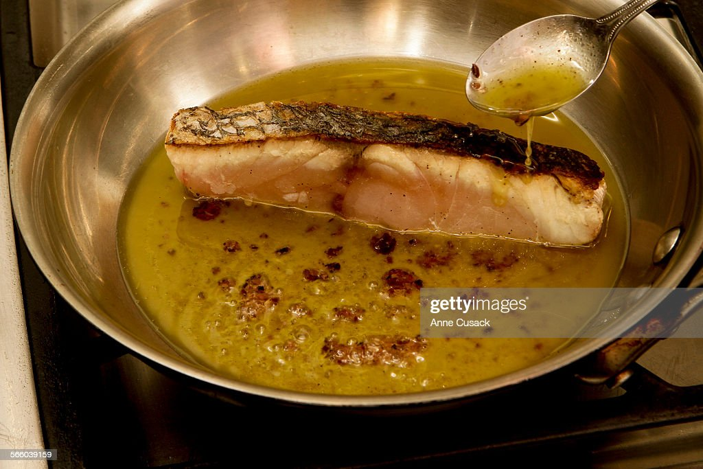 Basting the vinegarette over the fish as it cooks for Braised Sea Bass with Olive Vinegarette shot in the Los Angeles Times studio on June 9 2011