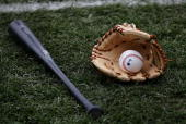 A bat glove and ball rest on the field before the Chicago Cubs' home opening game against the Houston Astros on April 9 2007 at Wrigley Field in...