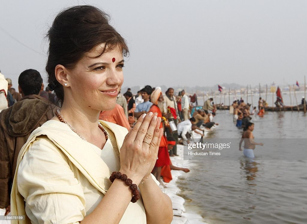 A batch of Foreigner devotees offer prayar at Sangam confluence of river Ganga, Yamuna and mythical Saraswati during Kumbh Mela, on January 16, 2013 in Allahabad, India. Kumbh is World's biggest religious gathering, in which more than 100 million of Hindus and sikh devotees will take part over next 55 days. Apart from being pilgrimage of faith, salvation and hope for millions of devotees, it also serve as meeting ground for the vast spectrum of Indian religious and spiritual views.
