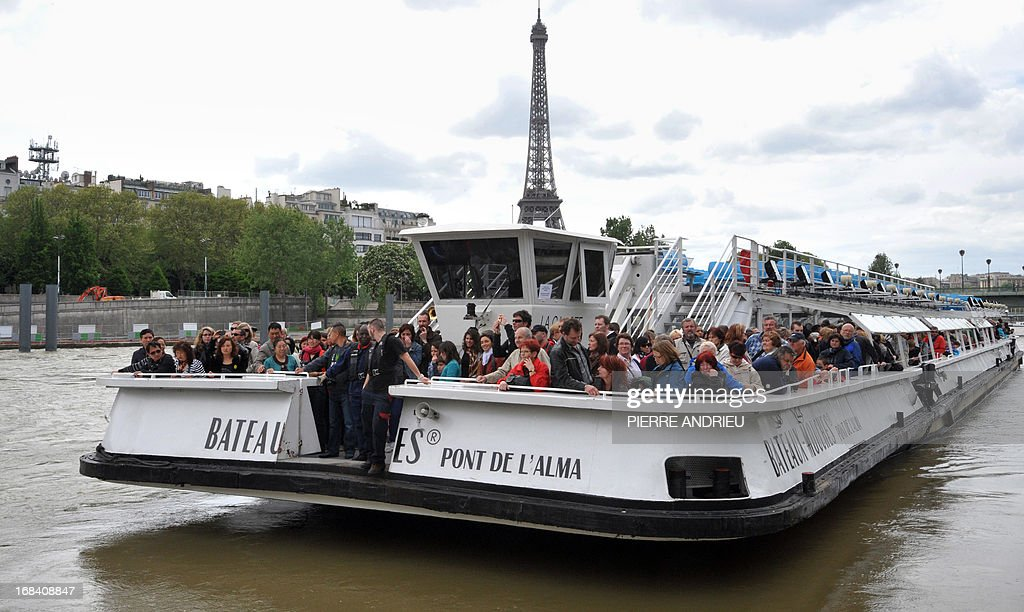 A 'Bateau Mouche' (Flying Boat) navigates carrying tourists on the Seine River on May 9, 2013 next to the Eiffel Tower in Paris. AFP PHOTO PIERRE ANDRIEU
