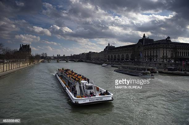 A 'BateauxMouches' a sightseeing riverboat cruise passes by on the river Seine in central Paris on February 13 2015 AFP PHOTO / MARTIN BUREAU