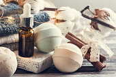 Bath spa accessories on rustic wooden table, beige green bombs, massage oil. Toned image