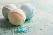 Bath bombs on blue concrete background and salt