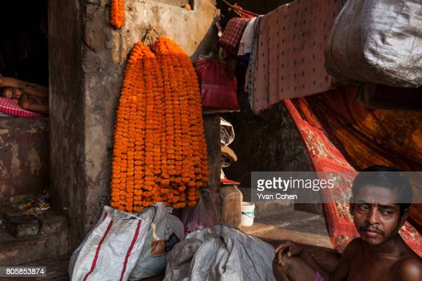 Bathed in late afternoon light a man rests in front of drying sarees flower garlands at Armenian ghat in Kolkata The capital of the Indian state of...