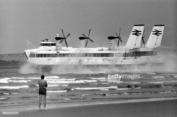 A bather on Boulonge beach France sees a new tourist attraction the world's largest Hovercraft the Mountbatten class SRN4 which made a preview trip...