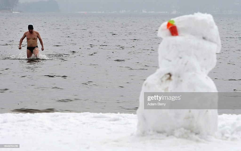 A bather wades from the water to the snow-covered Strandbad Wannsee beach where a headless Easter Bunny-shaped snowman stands during the beach's opening for the year on March 29, 2013 in Berlin, Germany. Despite continued unseasonably cold temperatures in the country, organizers opened the beach for bathers in time for the last weekend of March, when Easter Sunday is expected to be colder than the previous Christmas Day had been.