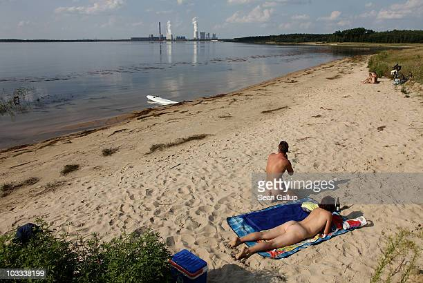 Bathers enjoy the beach at Baerwalder See lake as exhaust rises from the Boxberg coalburning power plant behind on August 10 2010 near Uhyst Germany...