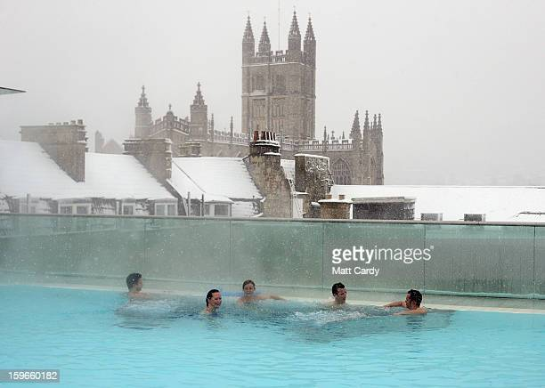 Bathers enjoy the rooftop pool at the Thermae Bath Spa as the snow continues to fall on January 18 2013 in Bath England Heavy snow is bringing...