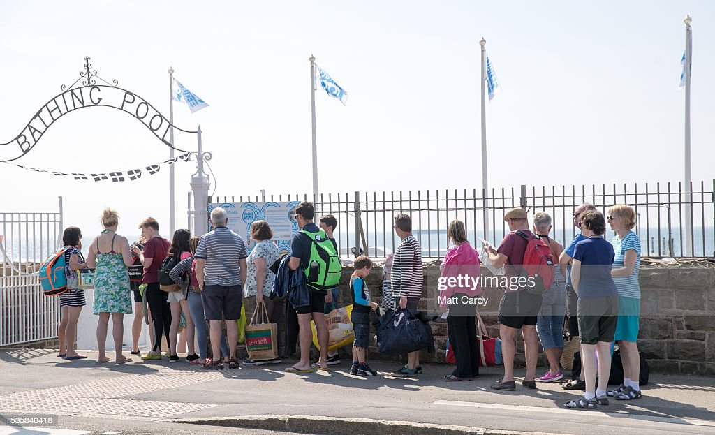 Bathers queue to enter the recently reopened Jubilee Pool lido in Penzance on May 30, 2016 in Cornwall, England. The Grade II Listed Art Deco seaside pool that suffered structural damage in the storms of early 2014, reopened this weekend after a £3million refurbishment. The pool, the UK's largest surviving seawater pool and an iconic feature of the seafront since it first opened in 1935, has recently announced future plans to heat part of the it with geothermal energy.