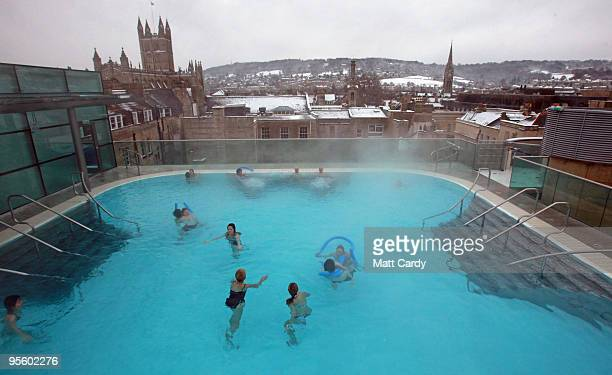 Bathers swim in the roof top pool of the Thermae Bath Spa enjoy the naturally heated spa water as snow sits on the rooftops of the city on January 6...