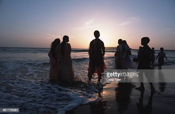 Bathers take a dip in the ocean at Goa a small seaside province in India's south Fully clothed in traditional Indian dresses it is very rare for...