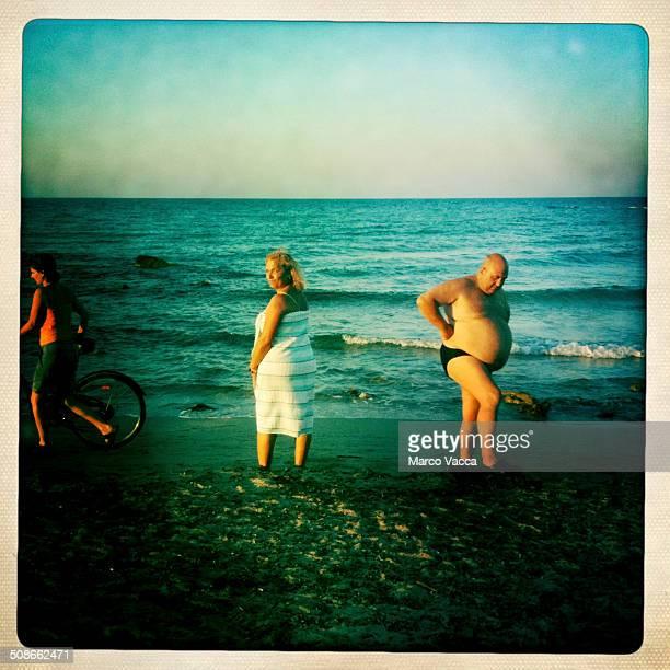 bathers walking along the shore in Salento coast near Brindisi Italy