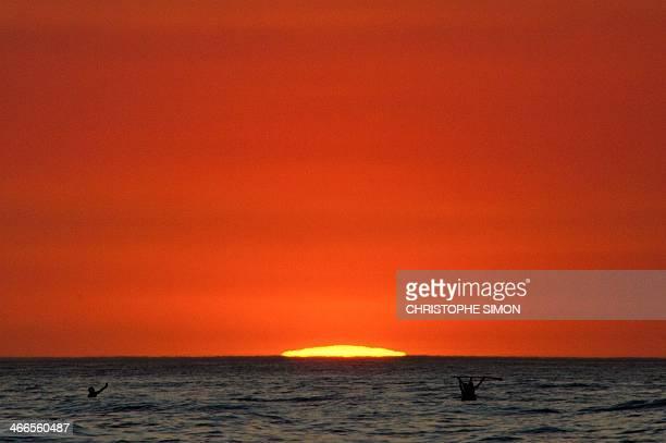 Bathers wave at Ipanema Beach at sunset in Rio de Janeiro Brazil on February 1 2014 AFP PHOTO / CHRISTOPHE SIMON