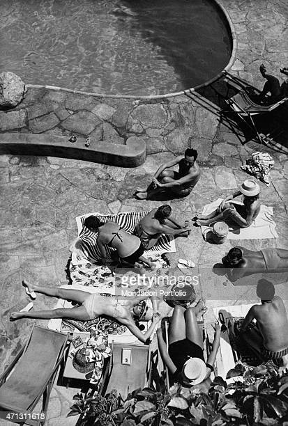 Bathers wearing their bathing suit at the poolside of the bathing establishment La canzone del mare the smartest hangout in Marina Piccola bay Capri...