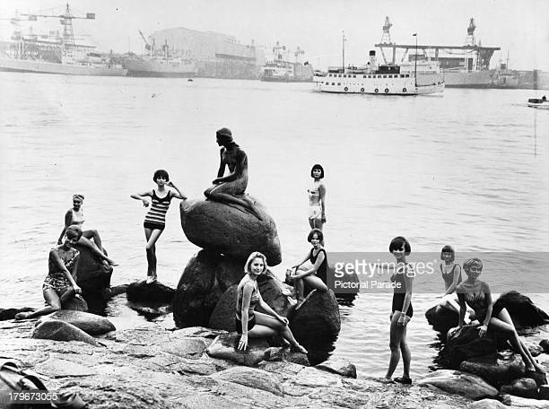 Bathing beauties pose with The Little Mermaid in Copenhagen Denmark