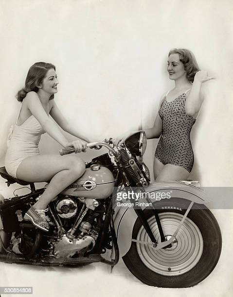A bathing beauty sits on a HarleyDavidson motorcycle while another woman stands beside Photograph circa 1940's