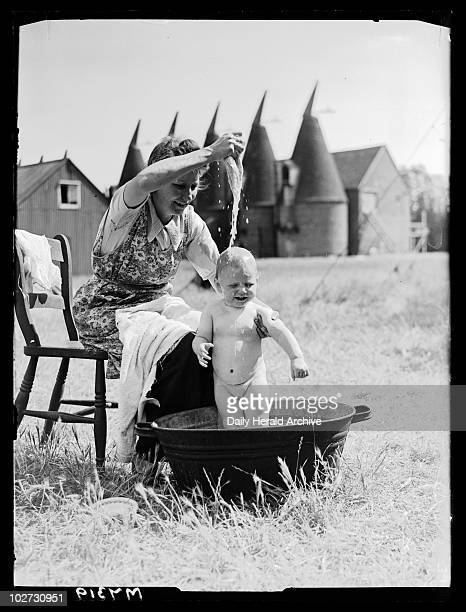 Bathing the baby 15 August 1944 A photograph of a woman bathing her baby girl outdoors in a tin bath taken by Nixon for the Daily Herald newspaper...