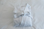 Folded spa Bathrobe : isolated  white bath robe folded on the bed in hotel room.  Prepare for shower and spa.