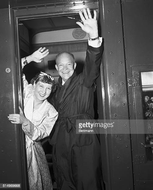 A bathrobeclad Dwight D Eisenhower and his wife waering a pink robe and her hair in curlers wave from the back platform of the GOP campaign train...