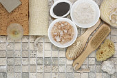 Set of bathroom accessory on stone tile: soaps, bath salt, clay, sponges, loofa. Top view point.
