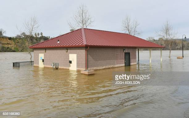 A bathroom building is seen partially submerged in flowing water at Riverbend Park in Oroville California on February 13 2017 Almost 200000 people...