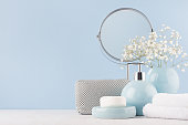 Bathroom decor for female in light soft blue color - circle mirror, silver cosmrtic bag, white flowers, towel, soap and ceramic smooth vase on white wood table.