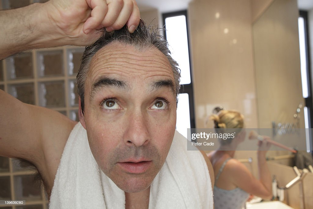 bathroom, man looking into camera/mirror : Stock Photo