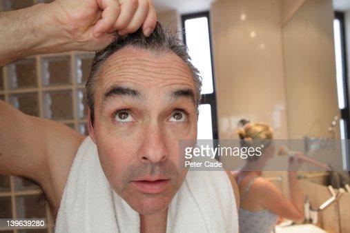 bathroom, man looking into camera/mirror : Stock Photo