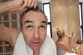bathroom, man looking into camera/mirror