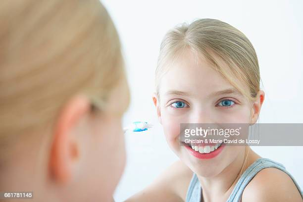 Bathroom mirror portrait of girl holding toothbrush