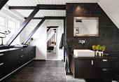 Bathroom in conjunction with bedroom. Structural beams, dark wood and granite tiles.