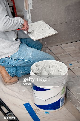 bathroom remodeling contractor putting mortar on tiles stock photo - Bathroom Remodeling Contractor