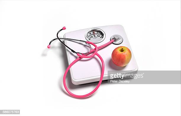 Bathroom scales with stethoscope and apple