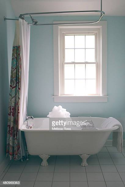 Bathroom with clawfoot tub filled with bubbles.