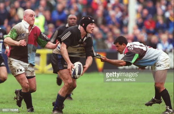 Bath's Russell Earnshaw looks to pass the ball as Harlequins' Keith Wood and John Schuster grab a piece of his shirt