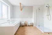 Bathtub and glass shower cabin in loft bathroom. Modern, bright attic apartment.