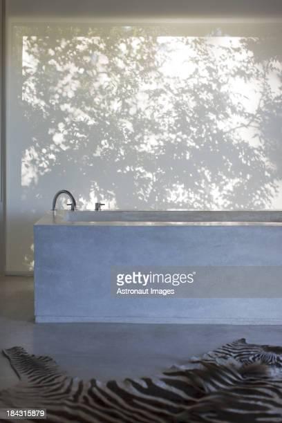 Tapis au motif zébré et baignoire dans la salle de bains moderne