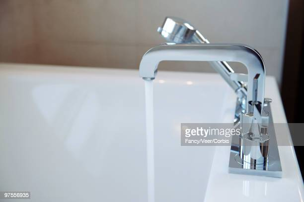 Bathtub faucet with water flowing into tub