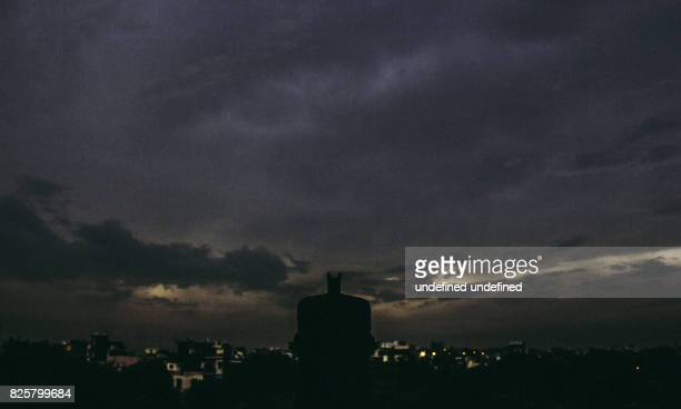 Batman watching over a city in a stormy night
