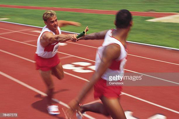 Baton being passed between runners