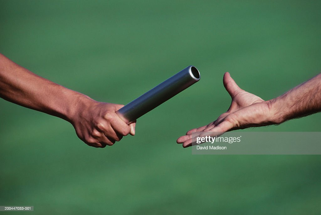 Baton change during relay race, close-up : Stock Photo