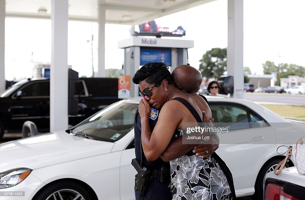 Baton Rouge Police Department Corporal Trina Dorsey hugs her brother Joseph Keller near a makeshift memorial for three police officers on July 19...