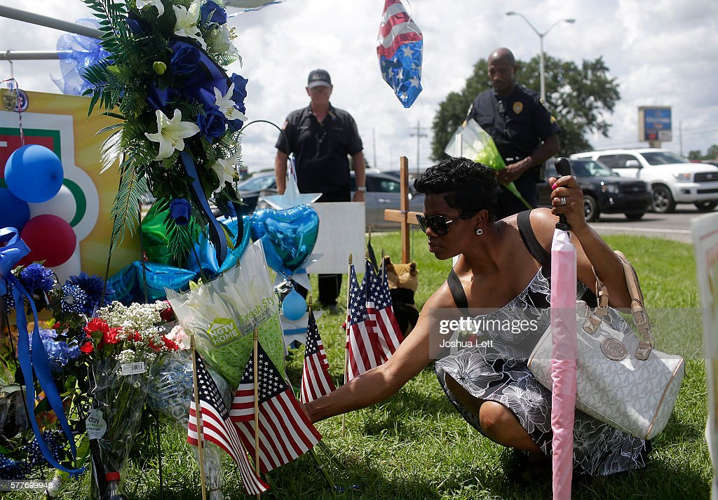 Baton Rouge Police Department Corporal Trina Dorsey places flowers at a makeshift memorial for three police officers as her brother and Baton Rouge...