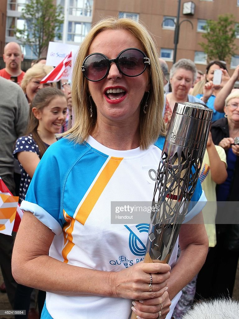 Batonbearer 031 Claire Grogan carries the Glasgow 2014 Queen's Baton through Johnstone in Renfrewshire on July 17, 2014 in Scotland. Scotland is nation 70 of 70 nations and territories the Queen's Baton will visit.