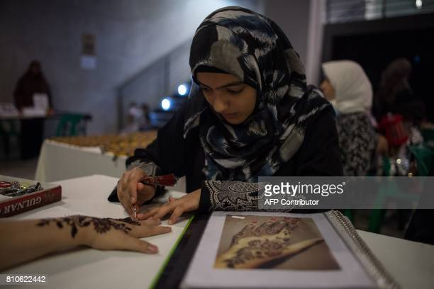 Batool Khashan a refugee from the Palestinian Territories living in Malaysia decorates a hand with henna at the refugee marketplace in Kuala Lumpur...