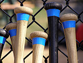 Baseball bats leaning against a batting cage.