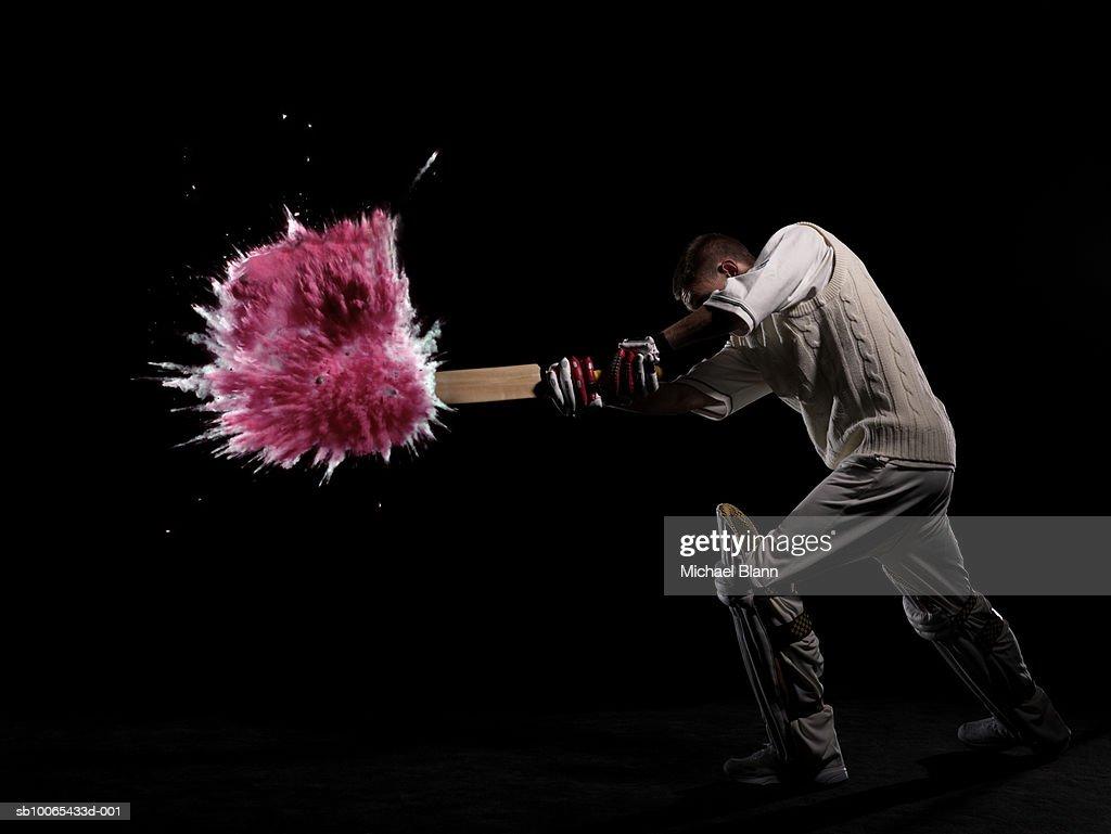 Batsman hitting exploding powder ball, side view, studio shot