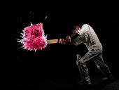 Batsman hitting exploding powder ball, side view, studio shot