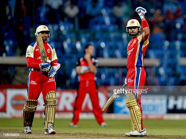 RCB batsman Virat Kholi raises his hand to acknowledge the crowd's applause after scoring 50 runs while his partnering batsman Tilakaratne Dilshaan...